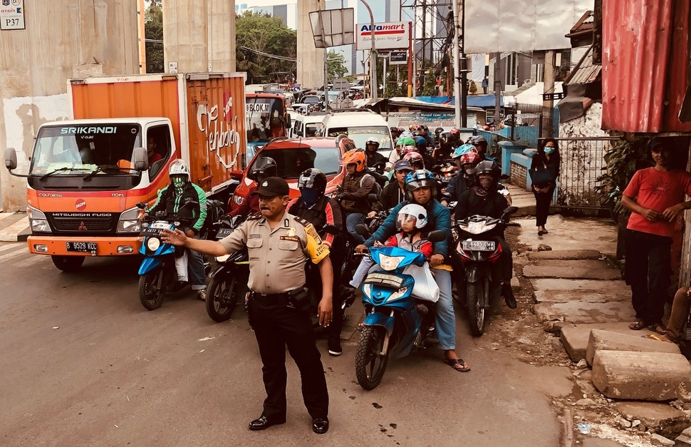 (Mike Stack | for The Salt Lake Tribune) Police officer holds back traffic in Jakarta, Indonesia, in October 2017