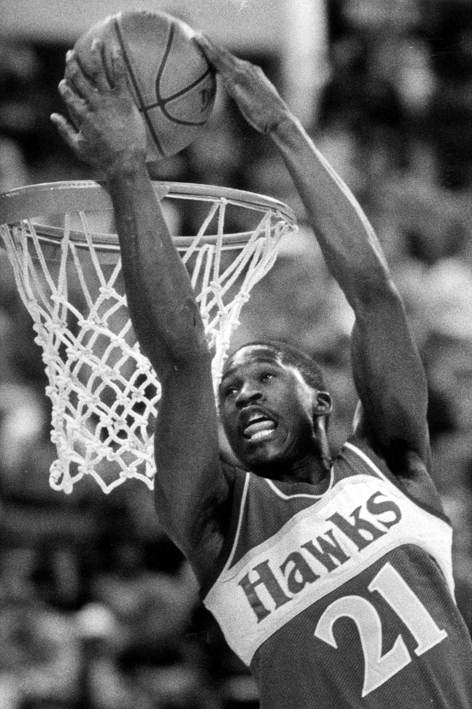 FILE - In this Feb. 9, 1985, file photo, Atlanta Hawks forward Dominique Wilkins dunks the ball over his head during the NBA Slam Dunk Contest in Indianapolis. Wilkins, an NBA Hall of Famer nicknamed The Human Highlight Film for his thunderous, acrobatic dunks during the 1980s and '90s, believes social media have amplified athletes' voices, and the Twitter-less past did not offer sports stars the soap boxes they have now. (AP Photo/Doug Atkins, File)