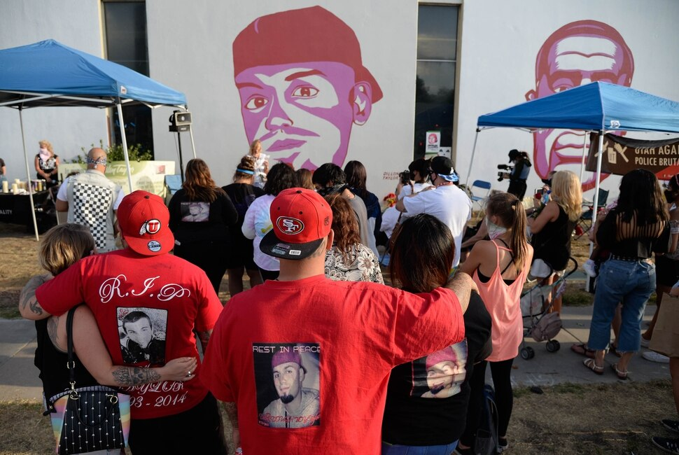 (Francisco Kjolseth | The Salt Lake Tribune) People gather for a vigil on the six-year anniversary of Dillon Taylor's death by the murals of people killed by police near 800 South and 300 West in Salt Lake City on Tuesday, August 11, 2020. Multiple families who's loved one's are depicted on the walls joined the vigil as they moved from portrait to portrait to remember them.