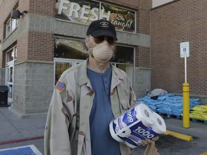 (Rick Bowmer | AP file photo) A Utahn wears a mask to protect against COVID-19 as he displays the toilet paper he purchased at a grocery store, March 17, 2020, in Salt Lake City. The Utah Department of Consumer Protection has fielded several complaints about high costs for toilet paper as the pandemic wears on. At least three proposed bills before the Legislature would change Utah's price gouging law.