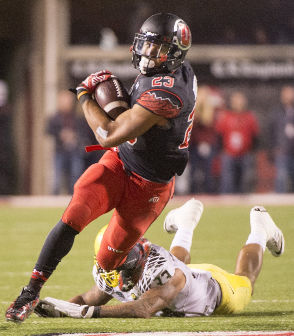 Rick Egan | The Salt Lake Tribune Ute running back Devontae Booker (23) slips out of the hands of Oregon Ducks linebacker Tyson Coleman (33) as he runs the ball into the end zone for a touchdown, in Pac-12 football action, Utah vs. Oregon game, at Rice-Eccles Stadium, Saturday, November 8, 2014