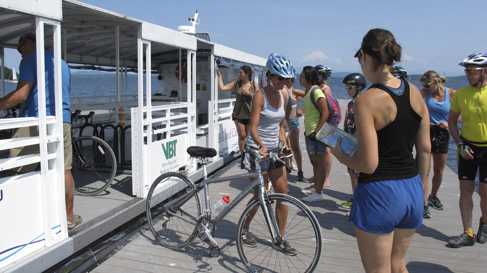 In this July 22, 2017 photo taken in South Hero, Vt., bicyclists collect their bicycles after taking a special ferry across a cut in an abandoned railroad causeway from the Vermont mainland to the Lake Champlain islands. The seasonal ferry on the three-mile section of the Island Line Trail bike path carries cyclists across the opening in the causeway so they can reach the islands. (AP Photo/Wilson Ring)