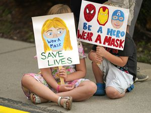 (Rick Bowmer | The Associated Press) Lucie Phillips, 6, and her brother David Phillips, 3, join parents and students during a rally at Utah State School Board Office calling for mask mandate Friday, Aug. 6, 2021, in Salt Lake City. The school year is days away for many kids in Utah and public health experts are worried about whether kids too young to get vaccinated will stay safe in school amid a wave of coronavirus cases.