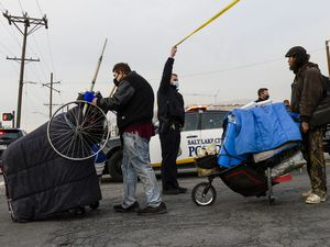 (Leah Hogsten  |  The Salt Lake Tribune) A Salt Lake City Police officer holds up police tape for two men leaving the Rio Grande area with their belongings, Dec. 10, 2020.