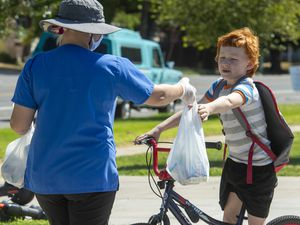 (Rick Egan     The Salt Lake Tribune)     Shayla Steinfels delivers lunches to student at Rose Park Elementary on Friday, Aug. 7, 2020.