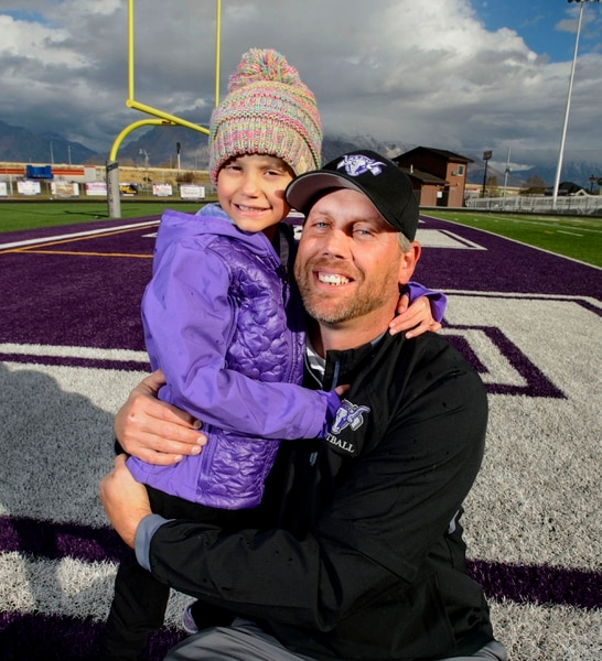 (Steve Griffin | The Salt Lake Tribune) Lehi assistant football coach Andy Hadfield with a his daughter Andelyn, age 5, on the school's football field in Lehi, Utah Sunday November 5, 2017. Andelyn is battling cancer and the football team has rallied around her.
