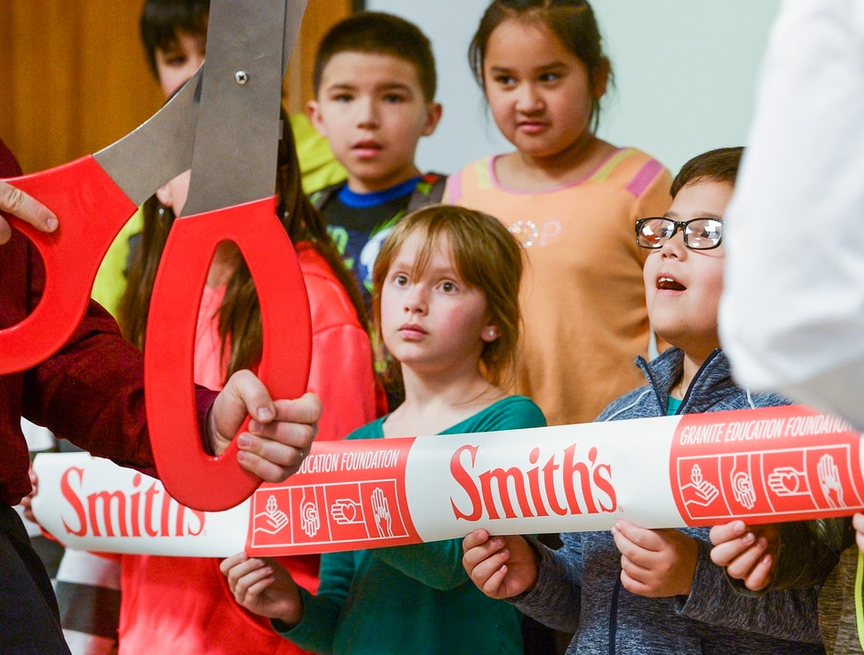 (Leah Hogsten | The Salt Lake Tribune) l-r The eyes of Ailie Spencer and Axel Godinez are as big as the ribbon cutting scissors, Tuesday, March 13, 2018 during a Smiths Food & Drug celebration and food pantry dedication at David Gourley Elementary School in Kearns, where 80 percent of the 646 students qualify for free or reduced lunches.