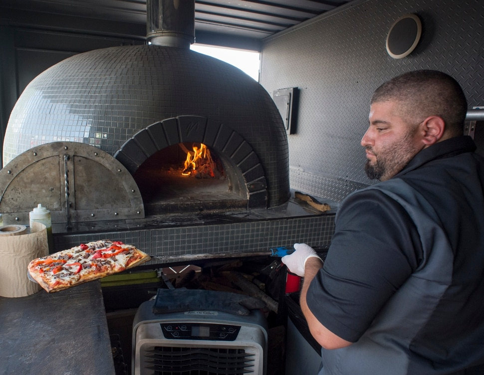 (Rick Egan | The Salt Lake Tribune) Fabio Marsenro removes a square pizza from the 4,000-pound wood-fired oven inside the Umani food truck.