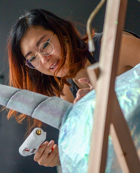 Leah Hogsten | The Salt Lake Tribune Cait Lee uses a hot glue gun to secure iridescent plastic sheeting to the sculpture of a narwhal. Lee is creating the scene of sea creatures flying through space at a vacant store in Gateway, April 12, 2019 as part of the Art Shop Project. The Art Shop Project at The Gateway was created to re-purpose and decorate vacant store windows with temporary art installations from local artists and students.