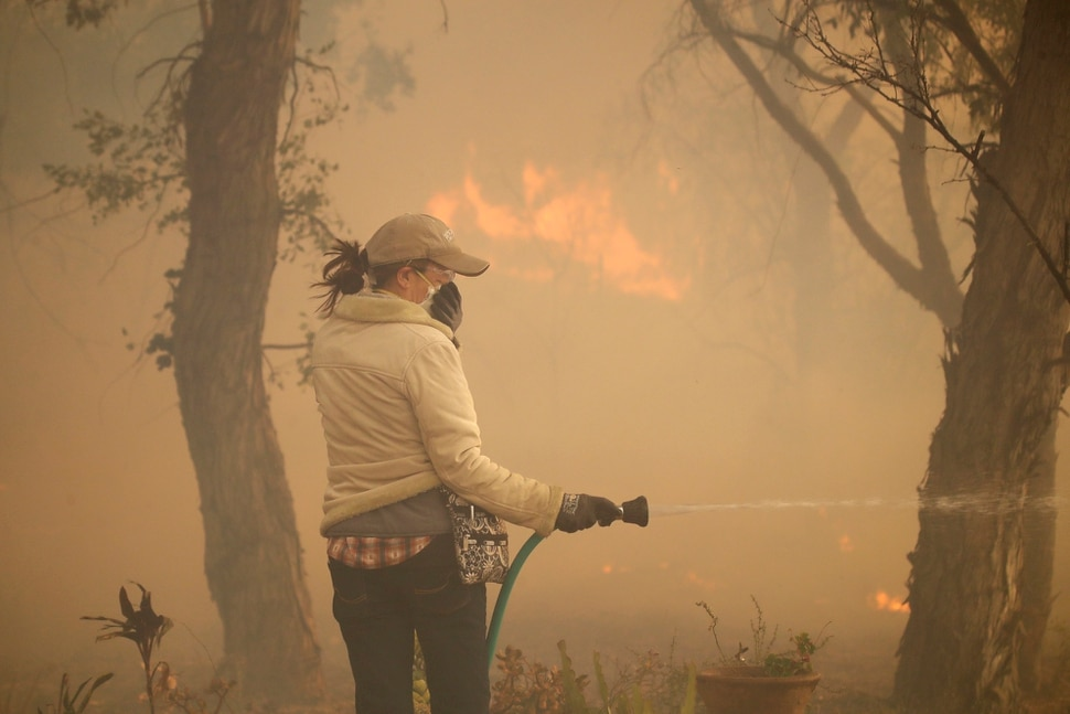 (Marcio Jose Sanchez | AP) Beth Rivera hoses down her property as the Easy fire approaches Wednesday, Oct. 30, 2019, in Simi Valley, Calif. Driven by powerful Santa Ana winds, the brush fire broke out before dawn between the cities of Simi Valley and Moorpark north of Los Angeles and exploded to more than 1,300 acres (526 hectares), threatening 6,500 homes, Ventura County officials said.