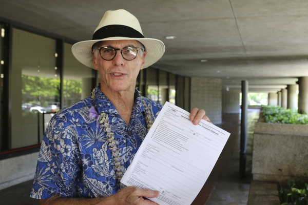 Gay-rights activist and Mormon critic Fred Karger stands outside the Federal Building in Honolulu on Thursday, Aug. 16, 2018, holding a complaint his group filed against the Mormon church with the U.S. Internal Revenue Service. Mormon critics are asking the IRS to investigate allegations that the church uses a Hawaii cultural center to commit tax fraud. (AP Photo/Jennifer Sinco Kelleher)