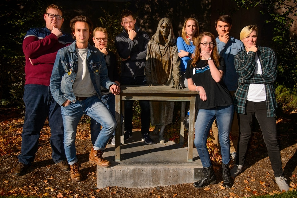 (Trent Nelson | The Salt Lake Tribune) The staff of The Alternate Universe, a website that makes fun of Provo and BYU culture, in Provo on Wednesday Oct. 30, 2019. The bronze they are posing with is Sleepwalking by James Avanti. From left, Thomas Richins, Taylor Garrett, Josh Newman, Stephen Fortuna, Mickey Randle, Dorian Baldwin-Bott, Adam Fletcher, and Michaela Rappleyea.