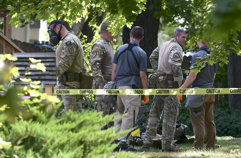 Law enforcement officers search a house on Wednesday, Oct. 3, 2018, in Logan, Utah. A man suspected of mailing ricin to the Pentagon and President Donald Trump was taken into custody at the scene. (Eli Lucero/Herald Journal via AP)