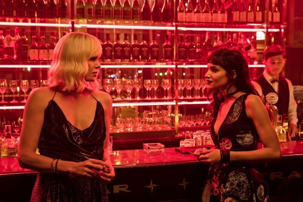 This image released by Focus Features shows Charlize Theron, left, and Sofia Boutella in