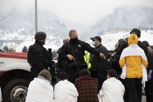 (Eliza Earle | The New York Times) Safety officials help people outside of the Boulder King Soopers grocery store after a shooting that killed multiple people in Boulder, Colo., on Monday, March 22, 2021.