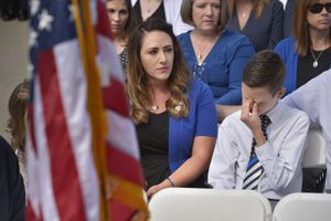 "(Scott Sommerdorf | The Salt Lake Tribune) Draper police Sgt. Derek Johnson's widow Shante Johnson sat with stepson Cayden Stone as they listened to Garon Brett sing ""Why"" at the Utah Law Enforcement Memorial, Thursday, May 3, 2018. No Utah law enforcement officer died in the line of duty last year."