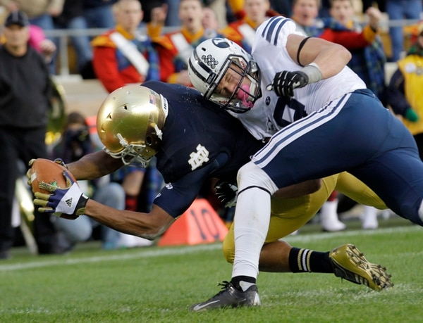 Notre Dame running back George Atkinson III is hit by BYU defensive back Daniel Sorensen as he dives in for a 20-yard touchdown run during the second half of an NCAA college football game in South Bend, Ind., Saturday, Oct. 20, 2012. Notre Dame defeated BYU 17-14. (AP Photo/Michael Conroy)