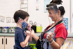 (Paul Bersebach  The Orange County Register) A student gets help with his mask from transitional kindergarten teacher Annette Cuccarese during the first day of classes at Tustin Ranch Elementary School in Tustin, Calif. Now that California schools have welcomed students back to in-person learning, they face a new challenge: A shortage of teachers and all other staff, the likes of which some districts say they've never seen.