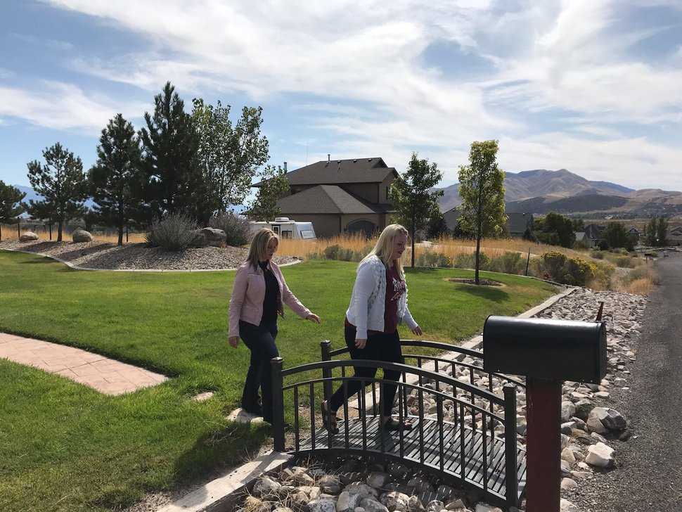 (Nate Carlisle | The Salt Lake Tribune) Angela Kelly, left, and Melissa Ellis cross a small bridge as they walk from a house in Eagle Mountain on Sept. 23, 2019. They work with a group called Sound Choices Coalition and went to a neighborhood with a high number of polygamists to ask what people there think of a proposal to lower the penalty for polygamy in Utah.