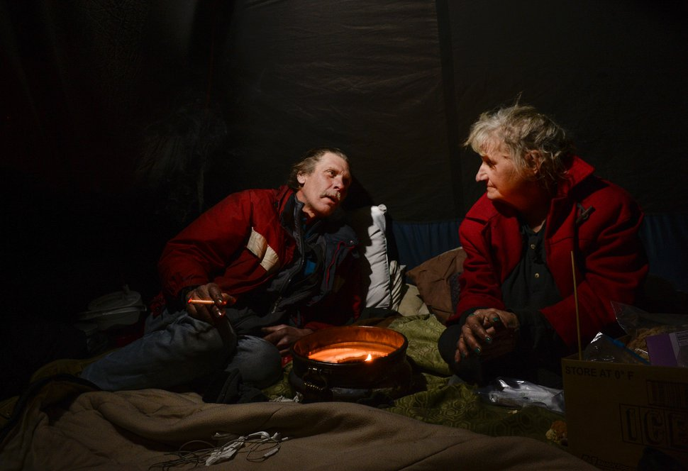 (Leah Hogsten | Tribune file photo) This Feb. 1 2019, file photo shows Ron Barrett, 55, and his wife Katherine Barrett, 54, who are homeless, trying to stay warm in their tent from the meager heat from a ceramic pot filled with candle wax. Their cold hands are blacken by the soot rising from the burning candle as temperatures dropped to 12 degrees in Salt Lake City. The Barretts later got into an apartment with the help of a federal housing voucher, but they've now been displaced because of a fire in the building this week.
