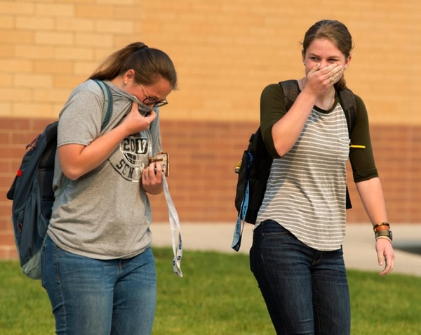 (Rick Egan | The Salt Lake Tribune) Salem High students Kylie Ovard, and Naomi Ellsworth cover their faces to combat the smokey air, as they head to lunch. Both of their families have been evacuated because of the Pole Creek fire, Friday, Sept. 14, 2018.