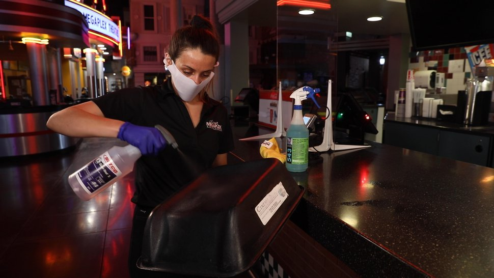 (Photo courtesy of Megaplex Theatres) An employee at the Megaplex Jordan Commons theater in Sandy sanitizes a booster seat. The Utah-based theater chain reopened 12 Utah locations on Thursday, June 18, 2020, three months after theaters were closed due to the coronavirus pandemic.
