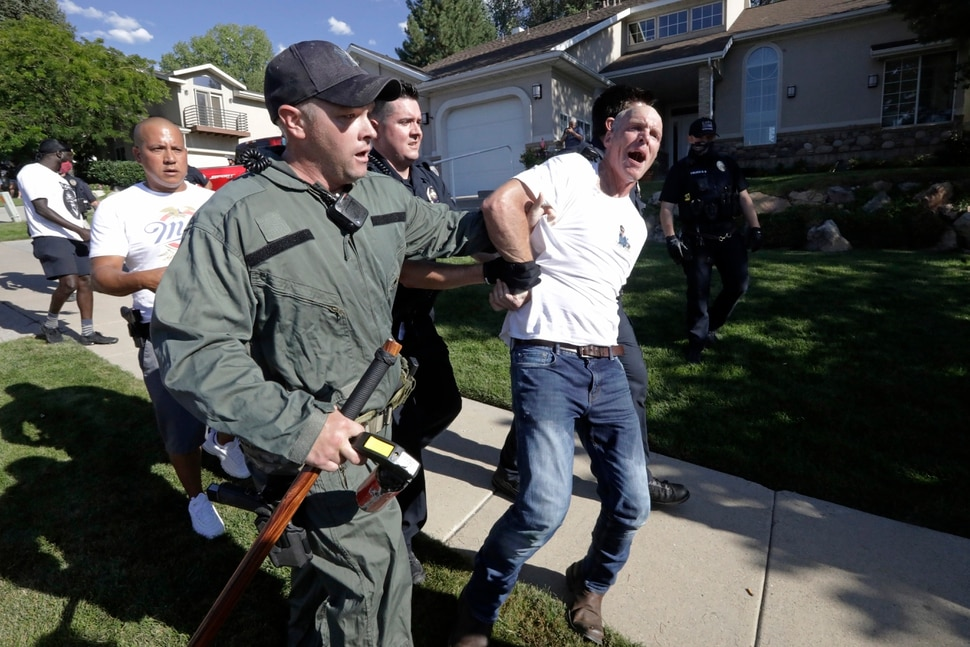 A protester is led away by Cottonwood Heights police officers during a march Sunday, Aug. 2, 2020, in Cottonwood Heights, Utah. The protest was a March for Justice focused largely around Zane James, who was fatally shot by police in Cottonwood Heights in 2018. (AP Photo/Rick Bowmer)