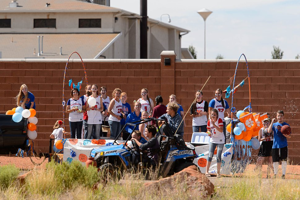 Trent Nelson | The Salt Lake Tribune Girls riding a float representing Snow Canyon High School launch a water fight with boys passing by at the end of the Colorado City and Hildale Fourth of July Parade in Hildale, UT, and Colorado City, AZ, Saturday July 2, 2016. At rear behind a large wall is the Leroy S. Johnson meetinghouse, used by the FLDS Church.