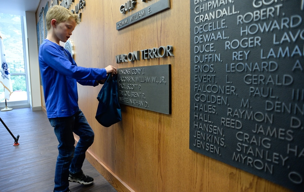 (Francisco Kjolseth | The Salt Lake Tribune) Jacob Taylor, 8, decides to keep all the bits and pieces of the small curtain that covered his late father's name, Major Brent Taylor now added to the Wilkinson Student Center Reflection RoomÕs Memorial Wall at Brigham Young University on Thursday, May 23, 2019. The former mayor of North Ogden and a BYU Army ROTC alumnus who was killed in Afghanistan in 2018, was honored by the BYU Army ROTC who added his name to the list of 211 who have died in service.