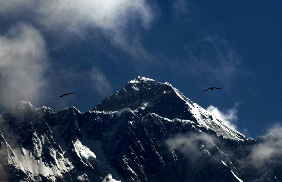 (Niranjan Shrestha   AP) In this Monday, May 27, 209, photo, birds fly as Mount Everest is seen from Namche Bajar, Solukhumbu district, Nepal. Seasoned mountaineers say the Nepal government's failure to limit the number of climbers on Mount Everest has resulted in dangerous overcrowding and a greater number of deaths.