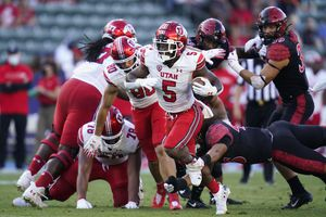 (Ashley Landis   AP) Utah running back TJ Pledger (5) is tripped up by San Diego State linebacker Michael Shawcroft (46) during the first half of an NCAA college football game Saturday, Sept. 18, 2021, in Carson, Calif.