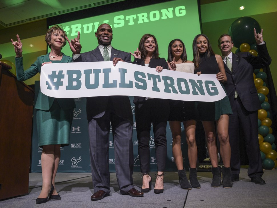 From left, University of South Florida President Judy Genshaft, new football coach Charlie Strong, his wife, Victoria, and daughters Hope and Hailee, and USF Athletic Director Mark Harlan, pose for a picture after an NCAA college football press conference at the Marshall Student Center at the University of South Florida in Tampa, Fla., on Thursday, Dec 15, 2016. (Andres Leiva/Tampa Bay Times via AP)