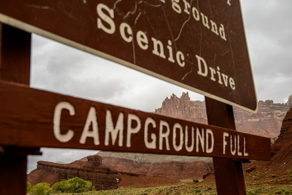 (Trent Nelson | The Salt Lake Tribune) The Castle at Capitol Reef National Park, seen through a sign indicating the campground is full, on Friday May 10, 2019.
