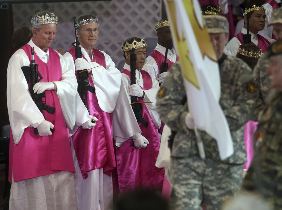 (AP Photo/Jacqueline Larma) Men wear crowns and hold unloaded weapons at the World Peace and Unification Sanctuary, Wednesday Feb. 28, 2018 in Newfoundland, Pa. Worshippers clutching AR-15 rifles participated in a commitment ceremony at the Pennsylvania-based church. The event Wednesday morning led a nearby school to cancel classes for the day. The church's leader, the Rev. Sean Moon, said in a prayer that God gave people the right to bear arms.