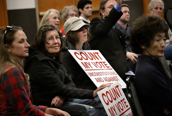 (Scott Sommerdorf | The Salt Lake Tribune) Some who came to the Count My Vote public hearing at the Whitmore Library in Cottonwood Heights brought signs voicing their displeasure with the Count My Vote ballot initiative seeking to select party nominees through a direct primary, and totally eliminate the traditional caucus-convention system, Friday, October 27, 2017.