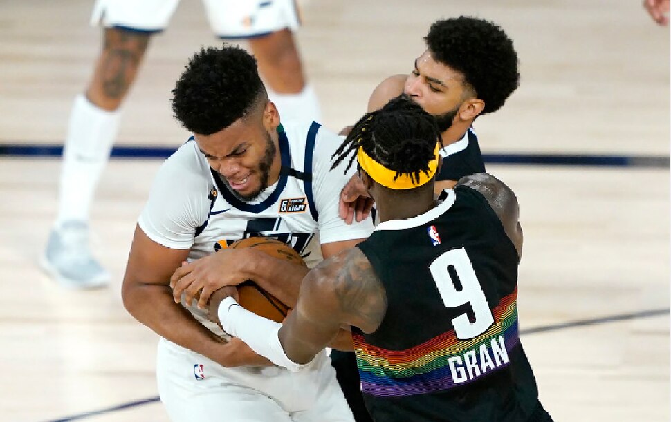Utah Jazz's Juwan Morgan, left, scrambles for the ball with Denver Nuggets' Jerami Grant (9) and Jamal Murray during the second half of an NBA basketball first round playoff game, Monday, Aug. 17, 2020, in Lake Buena Vista, Fla. (AP Photo/Ashley Landis, Pool)