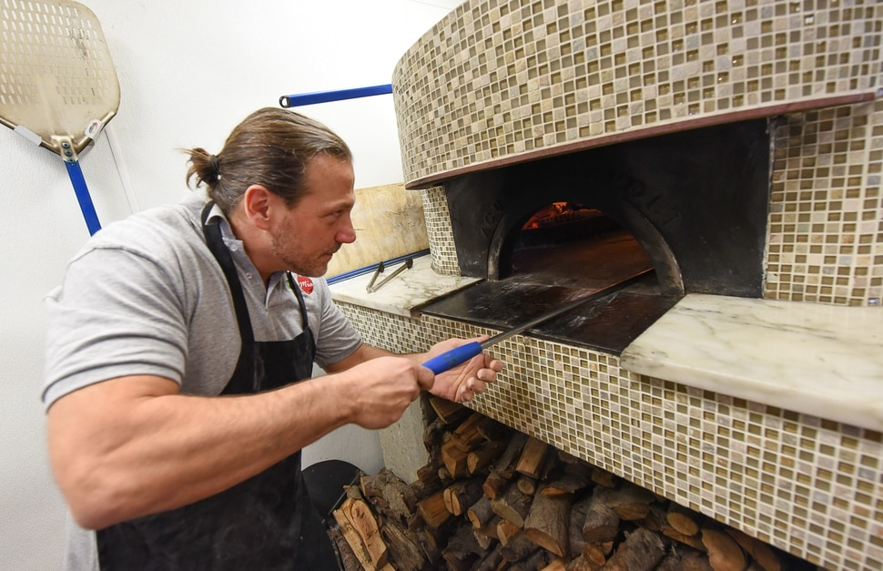 (Francisco Kjolseth | The Salt Lake Tribune) Ernesto Lo Russo, chef and owner of Terra Mia Italian restaurant in Draper, a sister restaurant to Terra Mia in Orem, rotates a wood fired pizza to reach perfection for customers during a recent lunch hour.