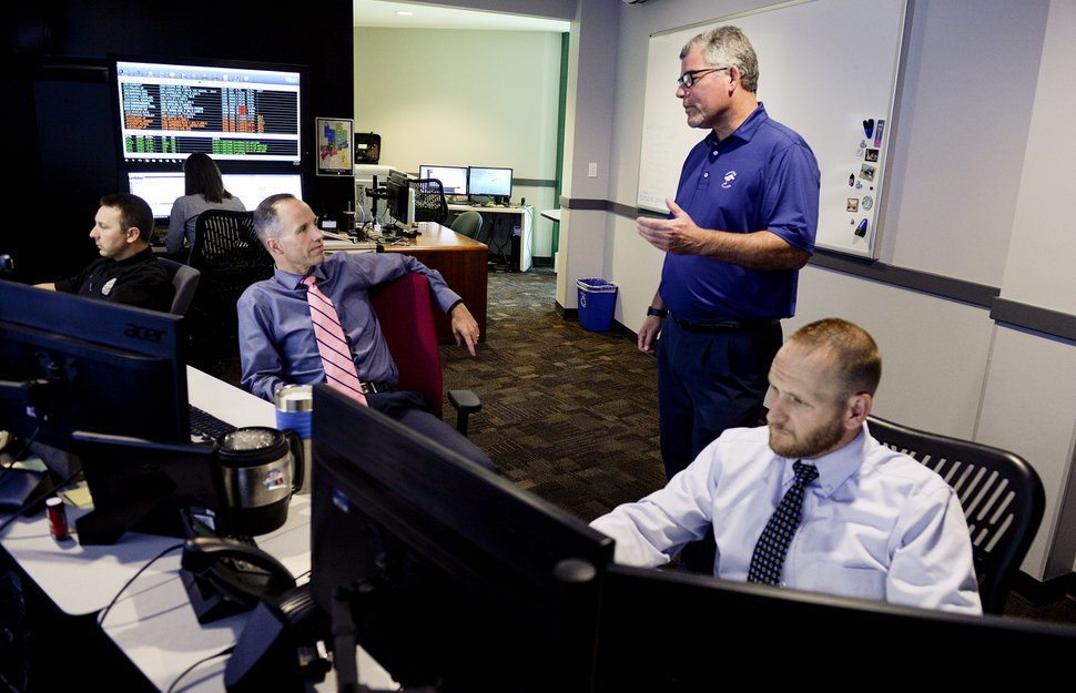 (Leah Hogsten | The Salt Lake Tribune) l-r ATAC director David Weloth, right, standing, talks with Ogden Police Department civilian crime analyst Jason Christensen in the ATAC center, October 1, 2019. Ogden Police Department's Area Tactical Analysis Center (ATAC) is staffed by three civilians and two OPD police detectives who monitor real time footage from the city's stationary and mobile cameras to assist officers on the frontline responding to crimes in progress and also detectives in the field, including from other agencies, to solve crimes.