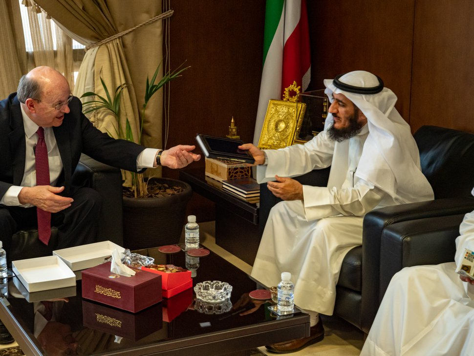 (Photo courtesy of The Church of Jesus Christ of Latter-day Saints) Apostle Quentin L. Cook gives a leather-bound Book of Mormon to Fareed Emadi, secretary-general of the Supreme Commission for the Promotion of Moderation in the Ministry of Awqaf, in Kuwait City on June 10, 2019.