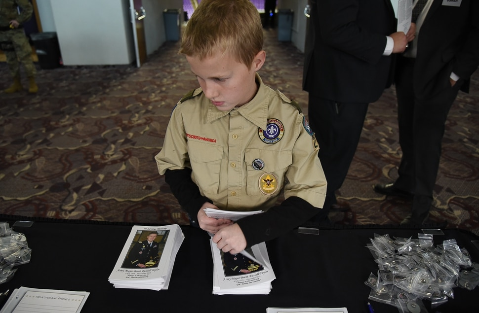 (Francisco Kjolseth | The Salt Lake Tribune) Isaac Franklin, 11, with scout troop 229, makes sure programs are not upside down before the start of funeral services for Maj Brent R. Taylo at Weber State UniversityÕs Dee Event Center in Ogden, Utah on Saturday, Nov. 17, 2018. Taylor, 39, the mayor of North Ogden, died Nov. 3, 2018, while serving in Afghanistan.
