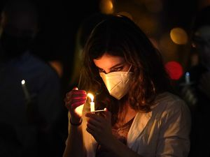 (Lynne Sladky | AP file photo)  A woman wears a protective face mask while holding a candle during an outdoor Christmas Eve Service of Lights at the Granada Presbyterian Church, Thursday, Dec. 24, 2020, in Coral Gables, Fla.