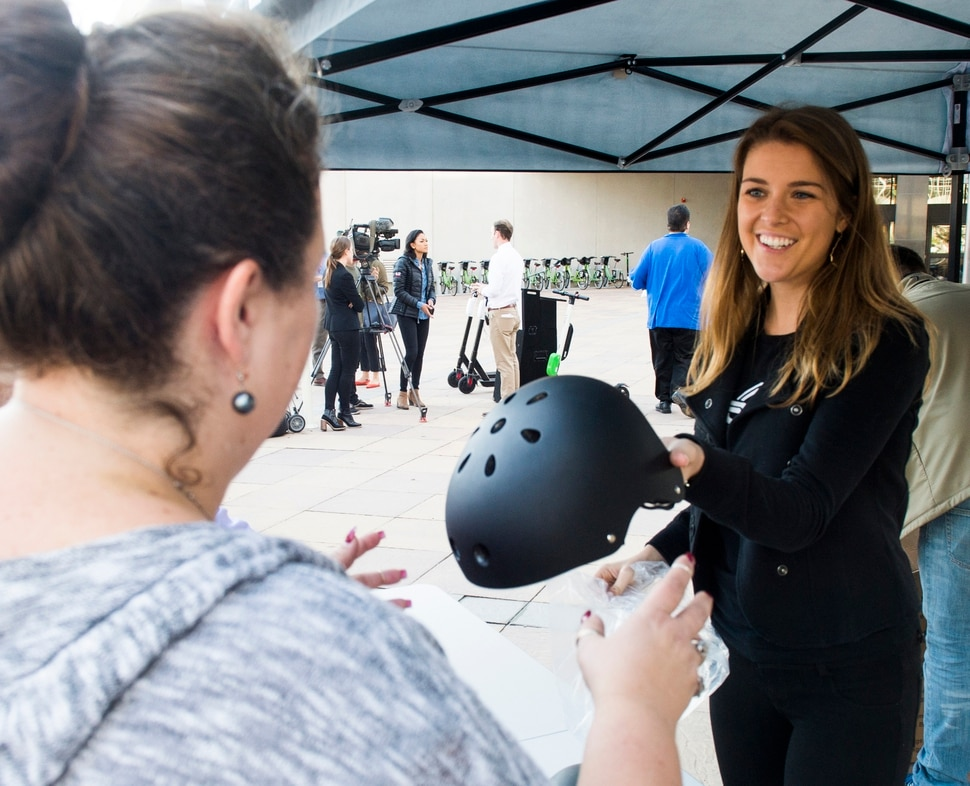 (Rick Egan | The Salt Lake Tribune) Kaitlyn Murray, passes out free helmets courtesy of Bird scooters, at a news conference, about the new campaign with e-scooter companies Lime and Bird in an effort to help residents and visitors understand the rules of the sidewalk, Wednesday, Oct. 3, 2018.