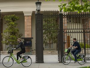 (Rick Egan     The Salt Lake Tribune)   Tourists wear masks as they ride bikes past the tabernacle in Salt Lake CIty, Wednesday, May 20, 2020.