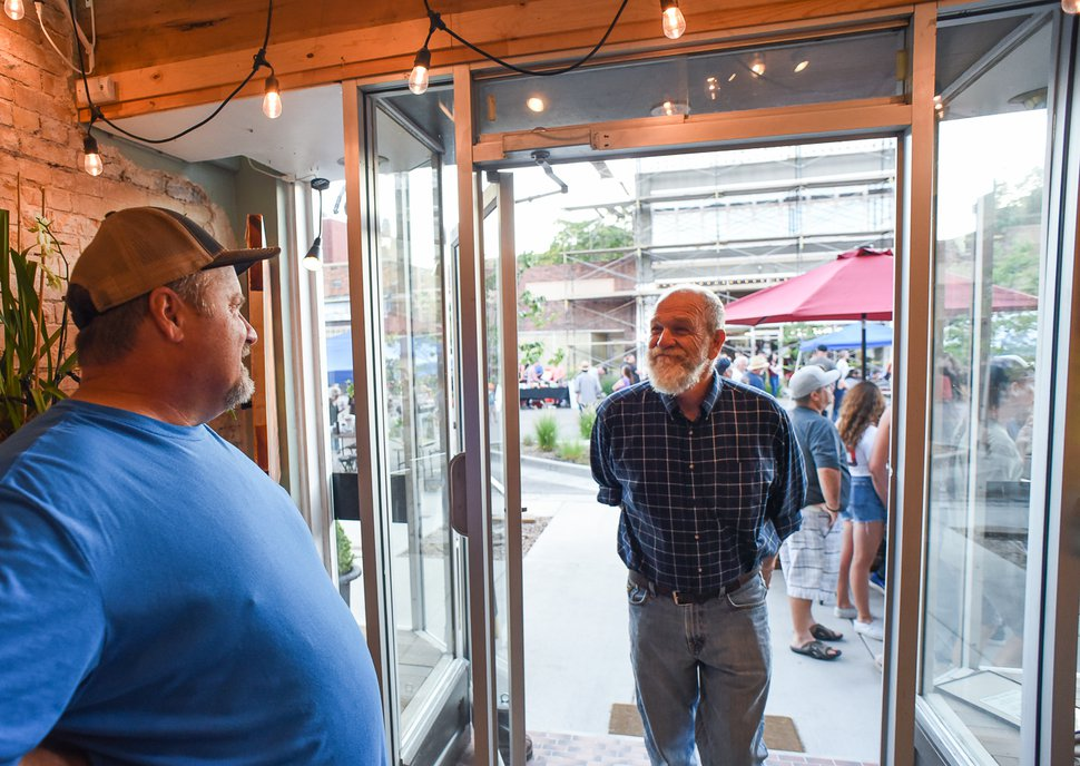 (Francisco Kjolseth | Tribune file photo) Clay Iorg, left, owner of The Balance Rock Eatery & Pub, visits with his neighbors, including artist David Richey Johnsen, Aug. 2, 2019. Iorg says his businesses have been hit hard by the pandemic.
