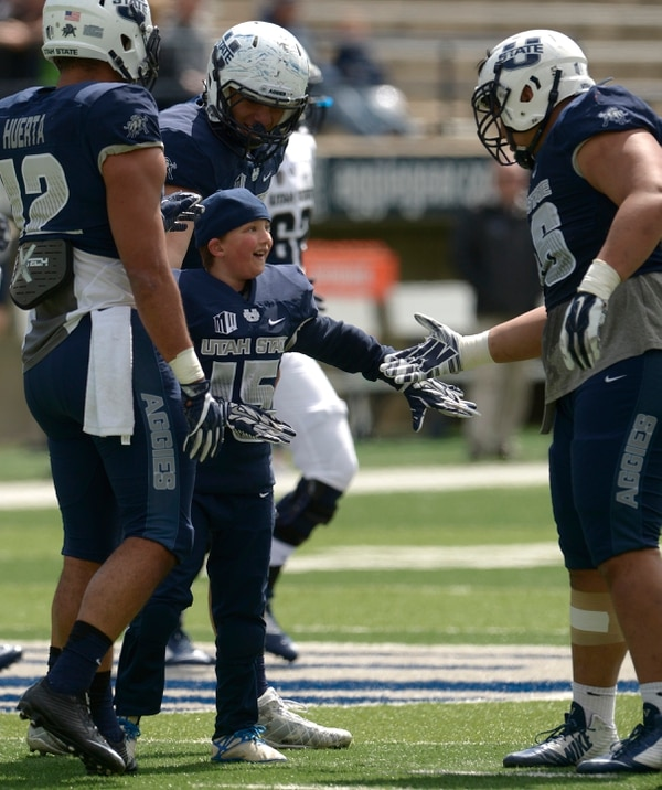 Leah Hogsten | The Salt Lake Tribune Jacob Knight, 11, got to meet the team and make a touchdown as running back for the Blue team during Utah State University football team's annual Blue vs. White Spring Game, Saturday, April 8, on Merlin Olsen Field at Maverik Stadium.