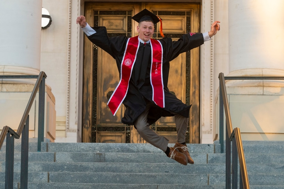 (Rick Egan | The Salt Lake Tribune) Spencer Brewster leaps in the air for a graduation picture in front of the Park Building at the University of Utah, Thursday April 30, 2020