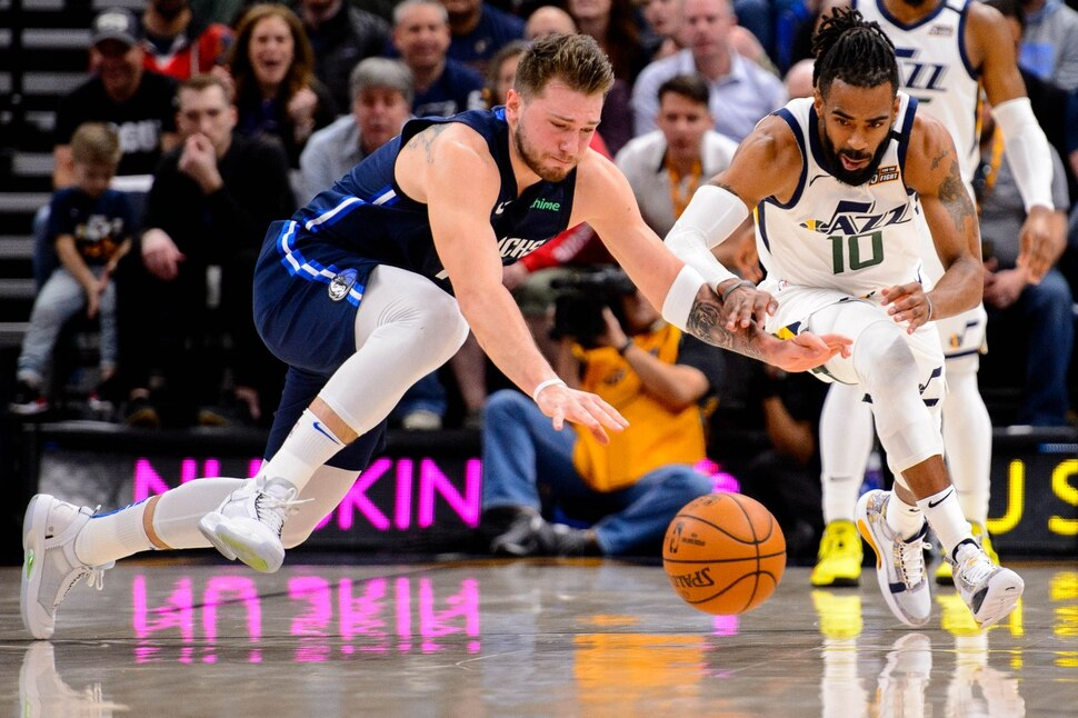 (Trent Nelson | The Salt Lake Tribune) Dallas Mavericks guard Luka Doncic (77) and Utah Jazz guard Mike Conley (10) dive for a loose ball as the Utah Jazz host the Dallas Mavericks, NBA basketball in Salt Lake City on Saturday, Jan. 25, 2020.