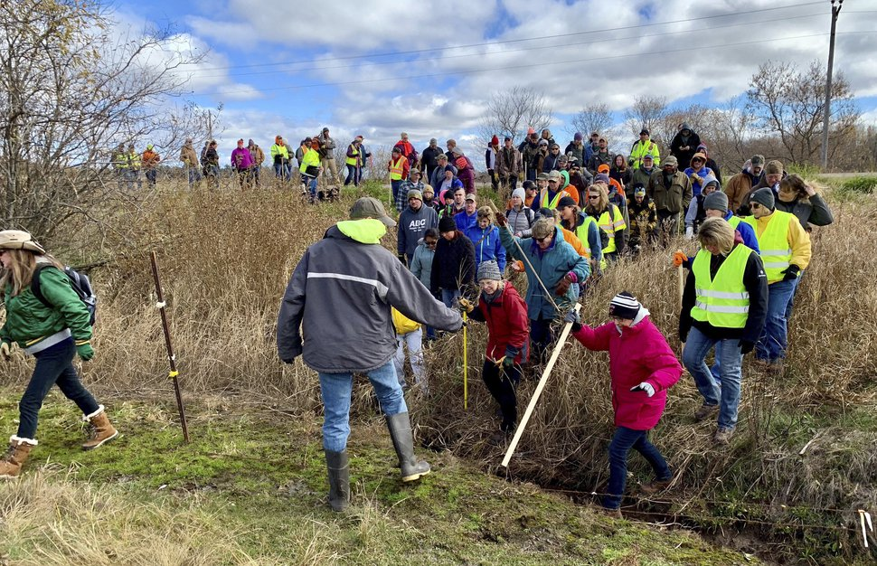 FILE - In this Oct. 23, 2018, file photo, volunteers cross a creek and barbed wire near Barron, Wis., on their way to a ground search for 13-year-old Jayme Closs who was discovered missing Oct. 15 after her parents were found fatally shot at their home. Wisconsin authorities are scaling back their ground search for Closs, saying their investigation into her abduction is entering a new phase. Incoming tips have declined, so authorities are transitioning from a round-the-clock reactive operation to a more methodical investigative approach. (AP Photo/Jeff Baenen, File)