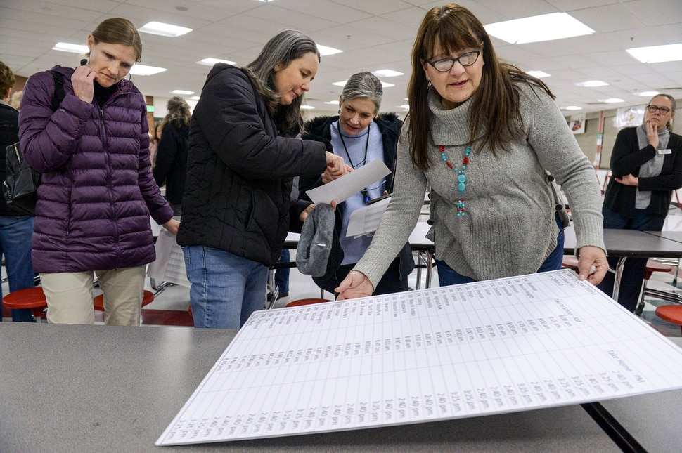 (Leah Hogsten | The Salt Lake Tribune) Allyson Maughan, (center, left) and Lori Meeleman (center, right) discuss how the new proposal would after their children as SLCSD board member Kristi Swett repositions a placard. The Salt Lake City Board of Education kicked off a listening tour Jan. 13, 2020 at Bryant Middle School to hear from students and parents about the possibility of implementing later school start times for the Salt Lake City school district high schools.