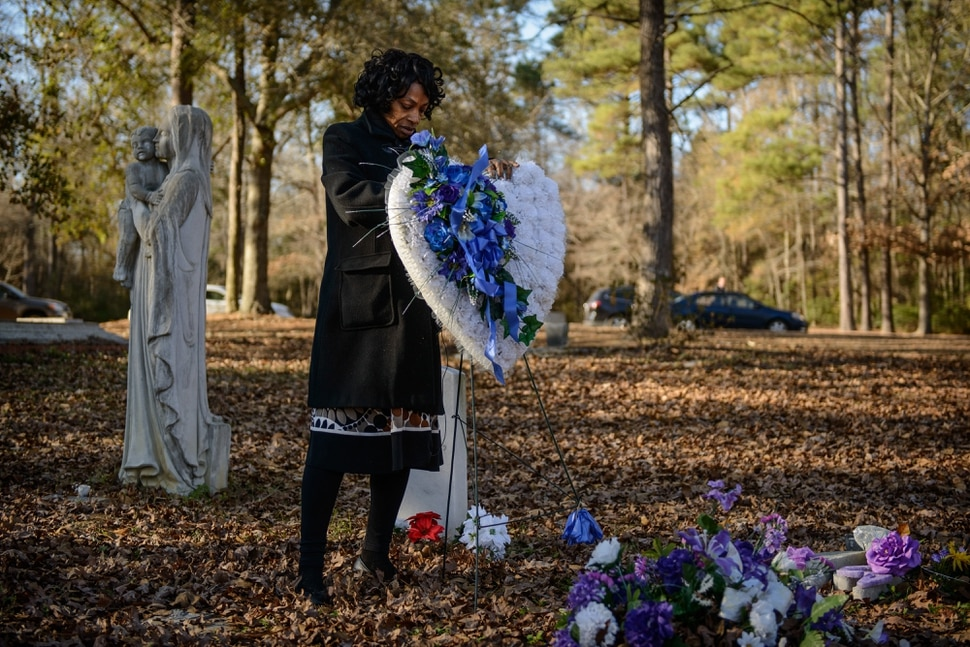 (Photo courtesy Washington Post/Sundnce Institute) Claudia Lacy places a flower memorial at the grave of her 17-year-old son Lennon Lacy, who was lynched in 2014 in North Carolina, in an image from Always In Season, by Jacqueline Olive, an official selection in the U.S. Documentary Competition of the 2019 Sundance Film Festival.
